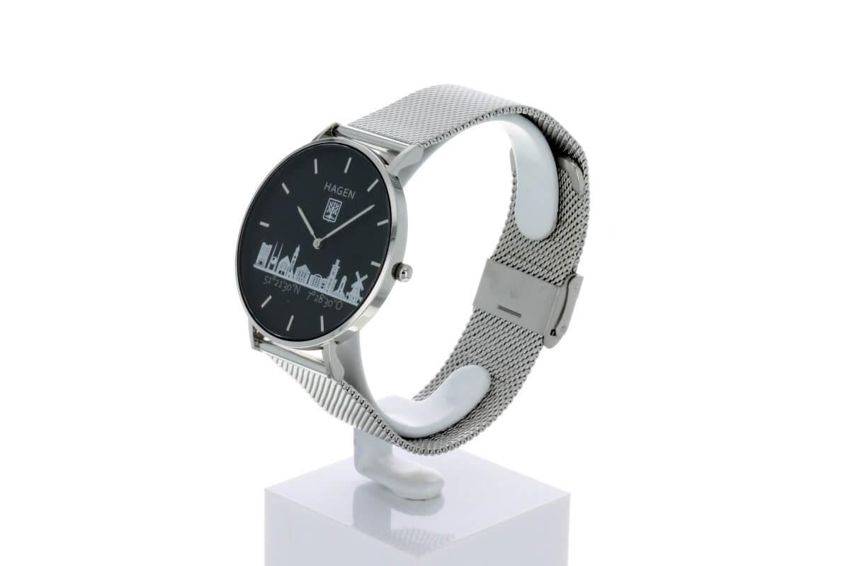 Hagen Uhr HagenUhr36MB in Edelstahloptik in 36mm Durchmesser mit Milanese Armband - Seiteliche Ansicht von Vorn, das schwarze Ziffernblatt und die Silbernen Ornamente sind gut zu sehen.