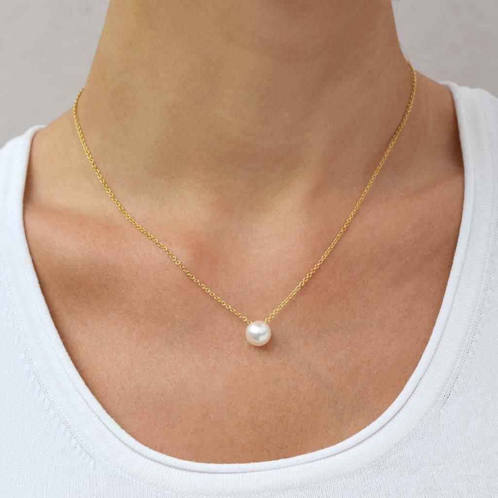 eva strepp ES_shop_c_spot-v Ein Model trägt eine vergoldete Kette mit einer weißen Zuchtperle